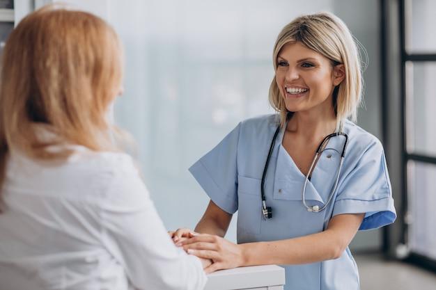 Jonge vrouwelijke arts met patiënt bij kliniek Gratis Foto