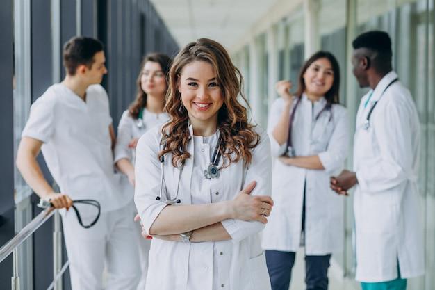 Jonge vrouwelijke arts poseren in de gang van het ziekenhuis Gratis Foto