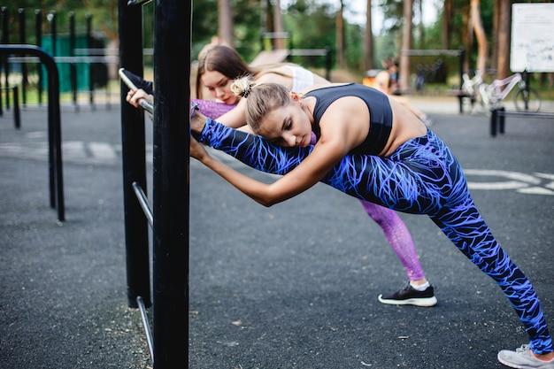 Jonge vrouwelijke atleten die zich vóór het lopen in park uitrekken. Premium Foto