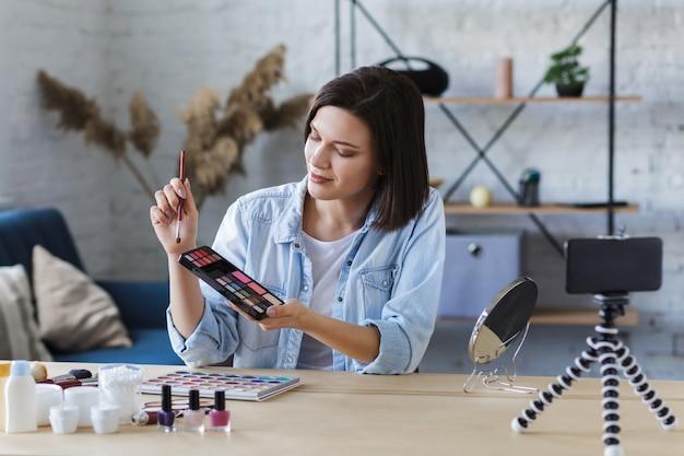 Jonge vrouwelijke blogger die een instructievideo opneemt voor haar beautyblog over cosmetica Premium Foto