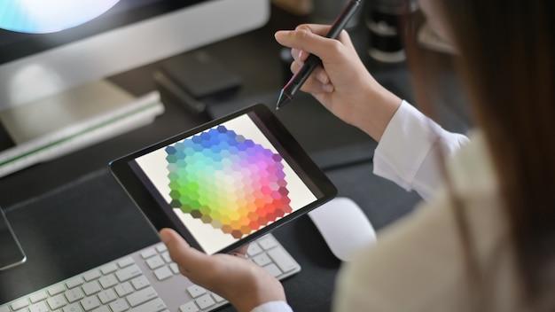 Jonge vrouwelijke creatieve kunstenaar van webdesign met het werken aan kleurselectie op grafische tablet. Premium Foto