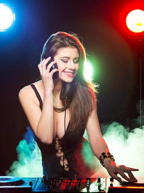 Jonge vrouwelijke dj op het werk in de club. Premium Foto