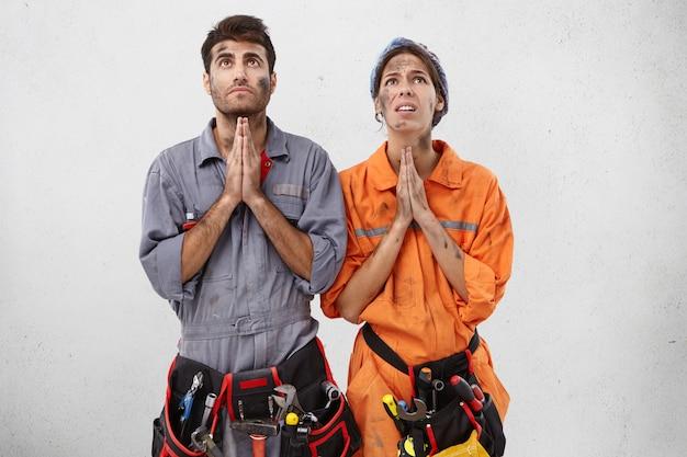 Jonge vrouwelijke en mannelijke loodgieters houden hun hand terwijl ze bidden Gratis Foto