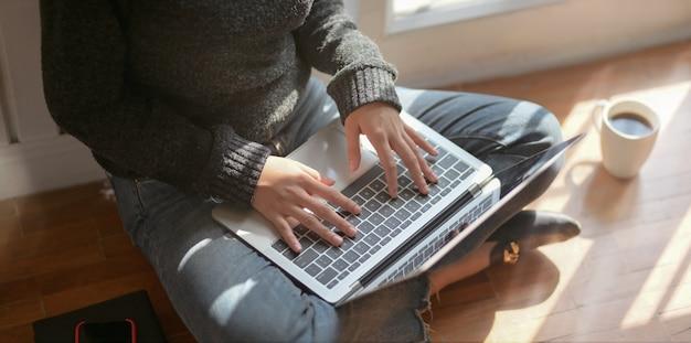 Jonge vrouwelijke freelancer te typen op een laptop tijdens de vergadering naast de ramen Premium Foto
