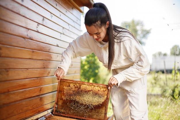 Jonge vrouwelijke imker trekt uit de korf een houten frame met honingraat. verzamel honing. bijenteelt. Premium Foto