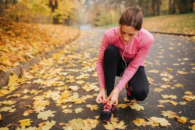 Jonge vrouwelijke jogger zit in squad positie en stropdas veters op haar schoenen. ze luistert naar muziek via een koptelefoon. jonge vrouw is geconcentreerd. Premium Foto