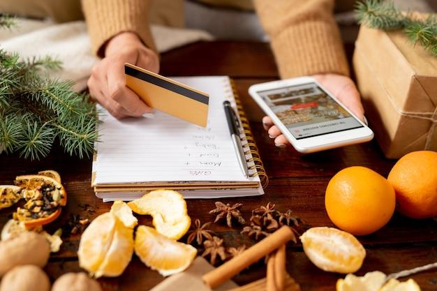 Jonge vrouwelijke klant creditcard en smartphone boven tafel te houden tijdens het bestellen van kerstcadeaus voor familie Premium Foto