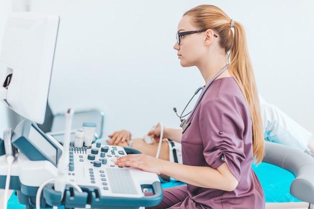 Jonge vrouwelijke londe arts met zwarte glazen. echografie scanner in handen van een arts. diagnostics. echografie. Premium Foto