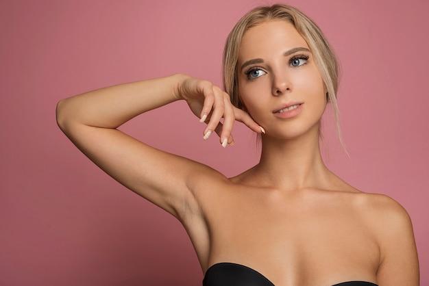 Jonge vrouwelijke model poseren op roze achtergrond Gratis Foto