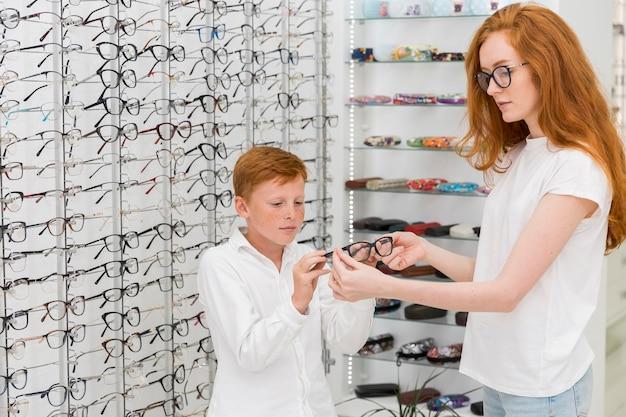 Jonge vrouwelijke opticien die schouwspel tonen aan jongen in opticaopslag Gratis Foto