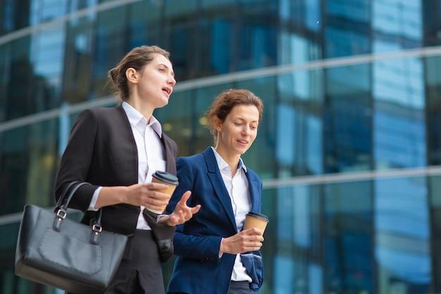 Jonge vrouwelijke professionals met afhaalmaaltijden koffiemokken dragen kantoorpakken, samen wandelen langs glazen kantoorgebouw, praten, project bespreken. gemiddeld schot. werkpauze of vriendschapsconcept Gratis Foto