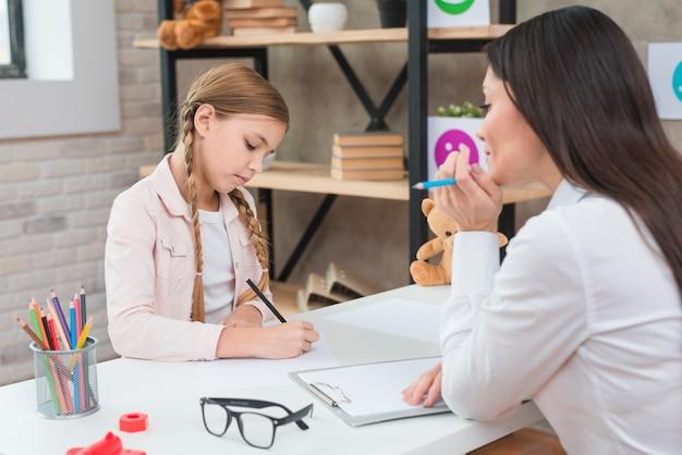 Jonge vrouwelijke psycholoog die het meisje waarnemen die op papier over de lijst trekken Gratis Foto