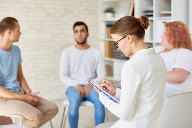 Jonge vrouwelijke psycholoog toonaangevende therapie sessie Premium Foto