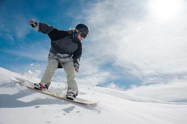 Jonge vrouwelijke snowboarder die de berghelling reduceert Premium Foto