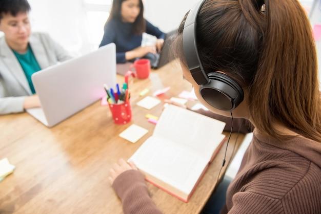 Jonge vrouwelijke student die hoofdtelefoon draagt en boek leest Premium Foto