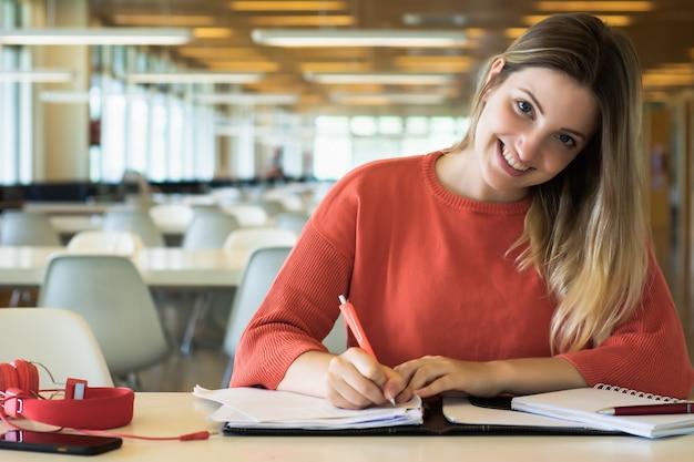 Jonge vrouwelijke student die in de bibliotheek bestudeert. Premium Foto