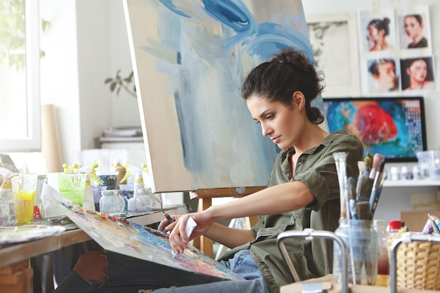 Jonge vrouwelijke student die lessen heeft in een kunststudio, leert landschappen te tekenen en probeert verschillende aquarellen op karton te mengen. geconcentreerde vrouw met donker haar, terloops gekleed, schilderen Gratis Foto