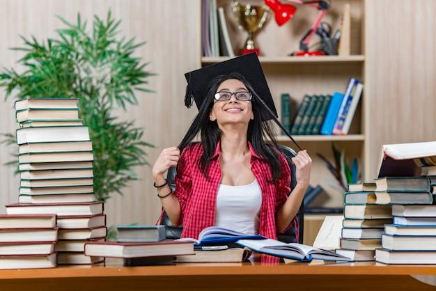 Jonge vrouwelijke student die voor universiteitsschoolexamens voorbereidingen treft Premium Foto
