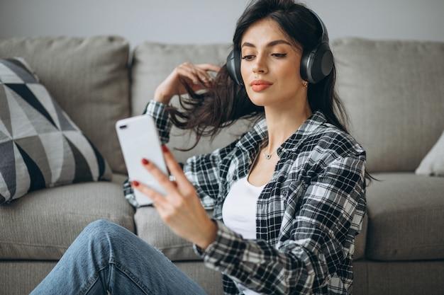 Jonge vrouwelijke student luisteren muziek via de telefoon op de koptelefoon Gratis Foto