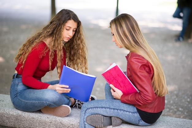 Jonge vrouwelijke studenten die samen in openlucht bestuderen Premium Foto