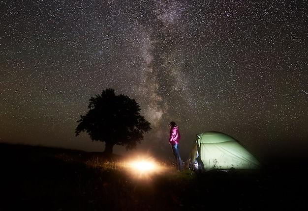 Jonge vrouwelijke toerist die dichtbij verlichte tent rusten, die in bergen bij nacht onder sterrige hemel kamperen Premium Foto