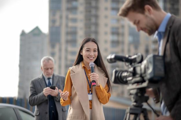 Jonge vrouwelijke verslaggever in een beige outfit praten met een camera Premium Foto