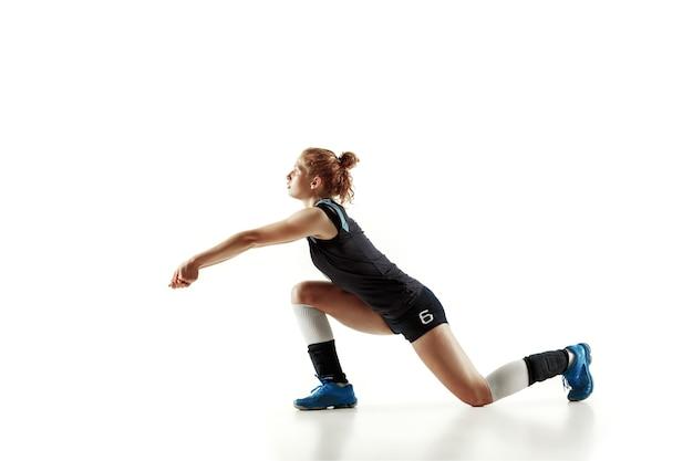 Jonge vrouwelijke volleyballspeler die op witte muur wordt geïsoleerd. vrouw in sportuitrusting en schoenen of sneakers trainen en oefenen. concept van sport, gezonde levensstijl, beweging en beweging. Gratis Foto