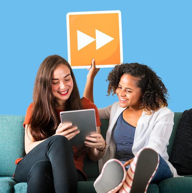 Jonge vrouwelijke vrienden houden een pictogram fast forward Gratis Foto