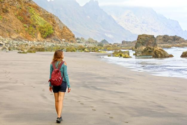 Jonge vrouwelijke wandelaar die wild paradijselijk strand op het eiland tenerife ontdekt Premium Foto