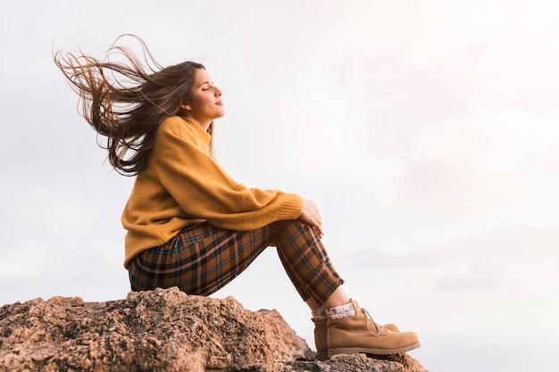 Jonge vrouwelijke wandelaarzitting bovenop rots die van de verse lucht genieten tegen hemel Premium Foto