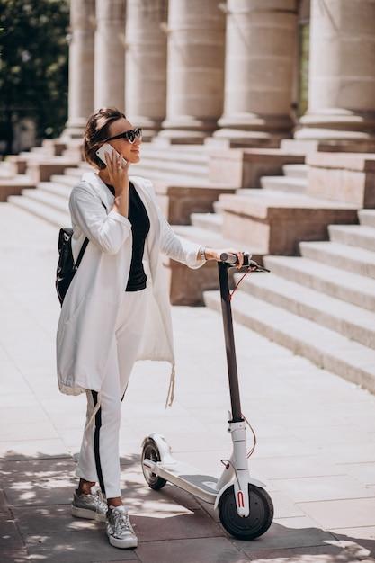 Jonge vrouwen berijdende scotter door het universitaire gebouw en het gebruiken van telefoon Gratis Foto