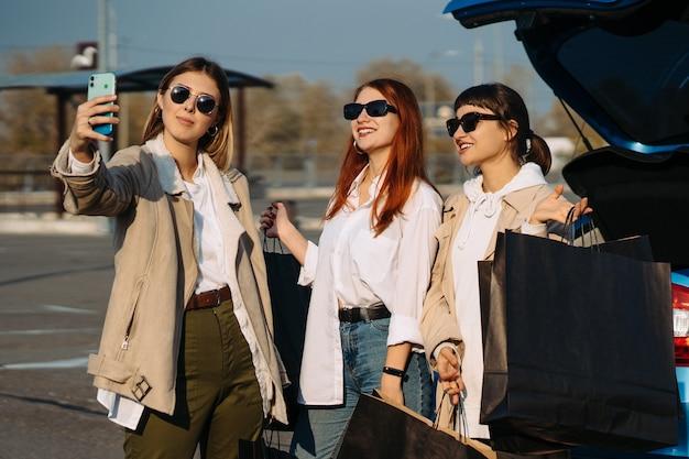 Jonge vrouwen bij de auto met boodschappentassen. meisjes nemen selfie Gratis Foto