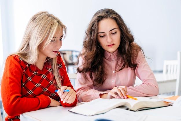 Jonge vrouwen die aan examen voorbereidingen treffen   Gratis Foto