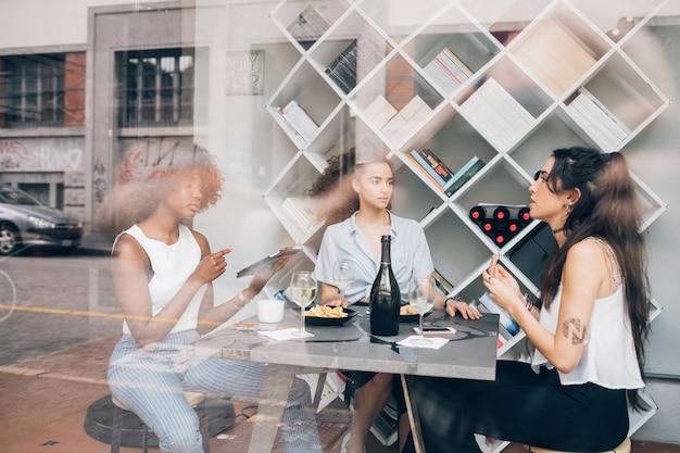 Jonge vrouwen die een onderbreking hebben die prosecco drinkt Premium Foto
