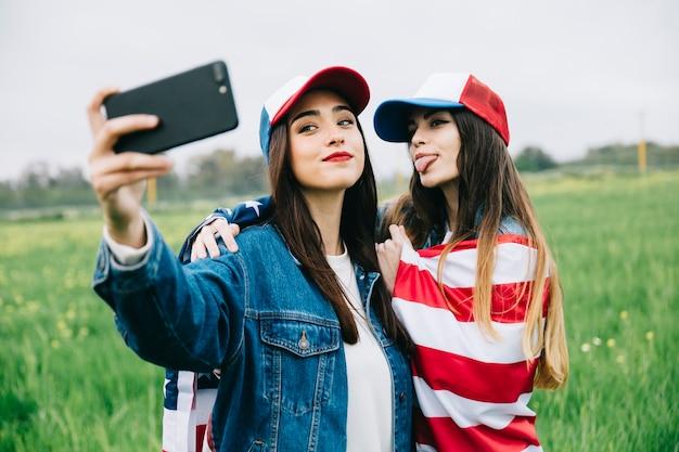 Jonge vrouwen die foto op telefoon buiten nemen Gratis Foto