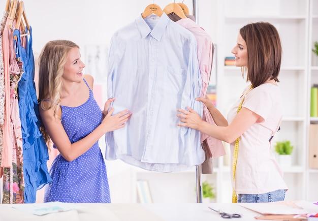 Jonge vrouwen die kleren op een rek in een toonzaal kiezen. Premium Foto
