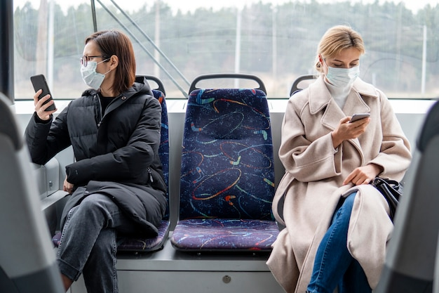 Jonge vrouwen die openbaar vervoer met chirurgisch masker gebruiken Gratis Foto