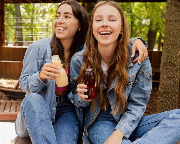 Jonge vrouwen die vers sapflessen houden en lachen Gratis Foto