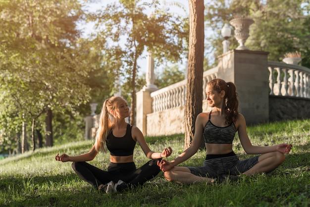 Jonge vrouwen die yoga in het park doen Gratis Foto