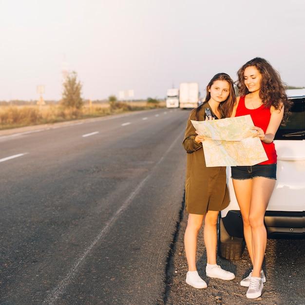 Jonge vrouwen die zich dichtbij witte auto met kaart bevinden Gratis Foto