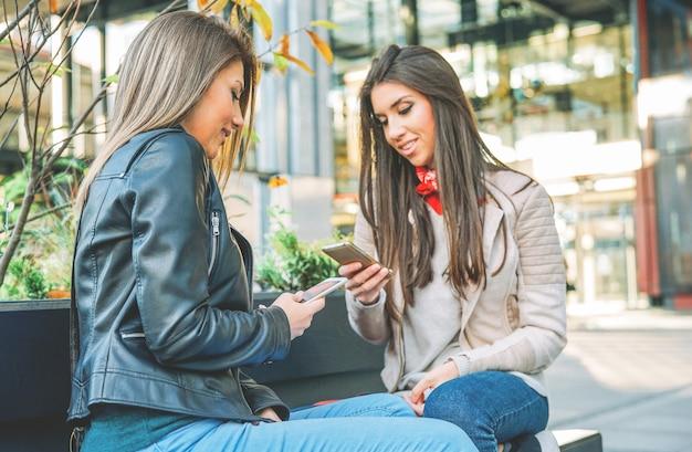 Jonge vrouwen die zich op een stedelijk gebied bevinden die met mobiele slimme telefoon in de stad verbinden openlucht Premium Foto