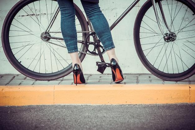 Jonge vrouwen en een fiets tegenover de stad Gratis Foto