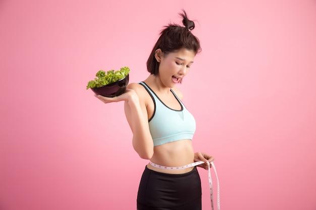 Jonge vrouwen eten graag groenten op een roze. Gratis Foto