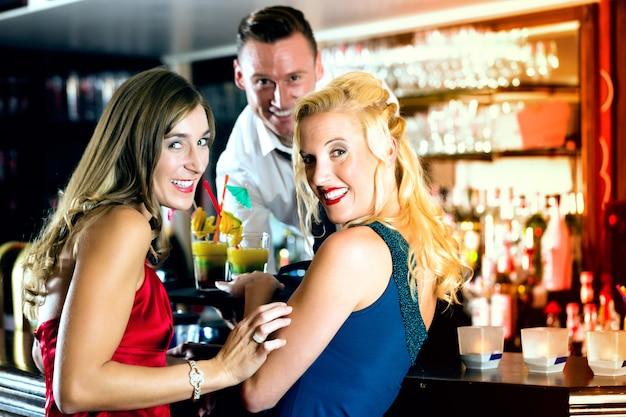 Jonge vrouwen in bar of club, de barman serveert cocktails Premium Foto