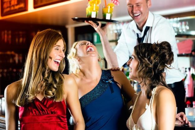 Jonge vrouwen in de bar of club plezier en lachen, de barman serveren cocktails Premium Foto