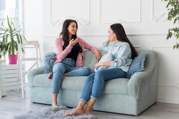 Jonge vrouwen praten zittend op de bank Gratis Foto
