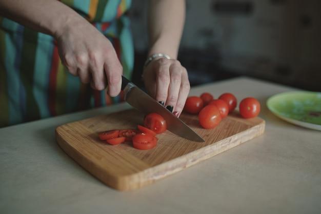Jonge vrouwen snijdende tomaten Gratis Foto