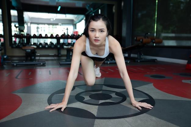 Jonge vrouwen worden opgewarmd voordat ze gaan sporten door de vloer te duwen en zijn knieën in de sportschool te buigen. Gratis Foto