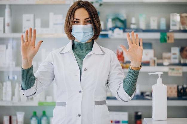 Jonge vrouwenapotheker die handen met sanitazer desinfecteert Gratis Foto