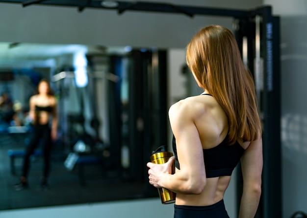 Jonge vrouwenbodybuilder in sportieve slijtage die zich voor de spiegel met fles bevinden Premium Foto